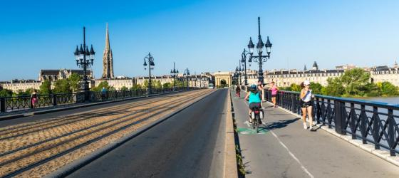 Cyclists crossing the Pont de Pierre, Bordeaux beside the Garonne River