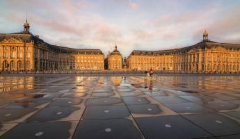 Biking past the Place de la Bourse in Bordeaux