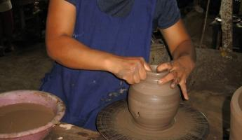 making the pottery, a potters wheel spun by foot