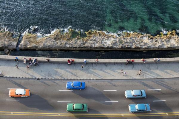 Vintage American cars speeding along the Malecon in Havana, Cuba