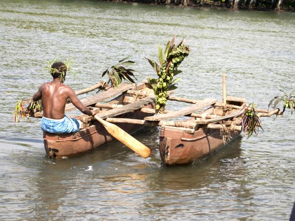 A tribal man pushing two canoes