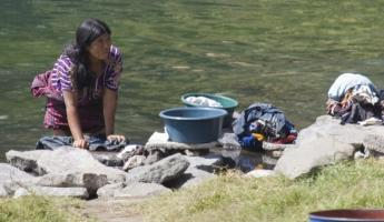 A woman washes her clothes in the river