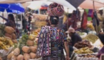 A woman balances her goods on her head