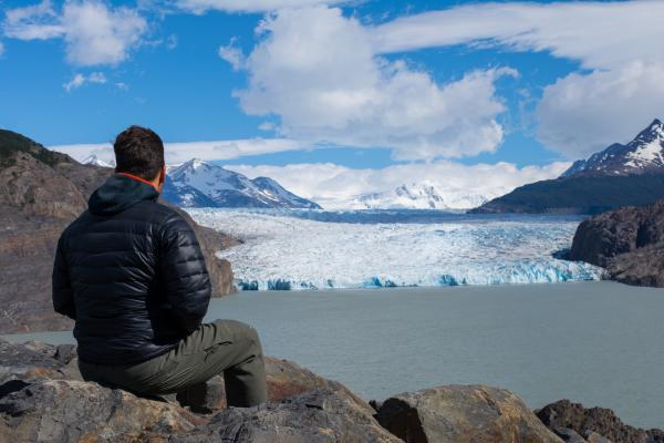 An O Trek hiker looks out at Grey Glacier