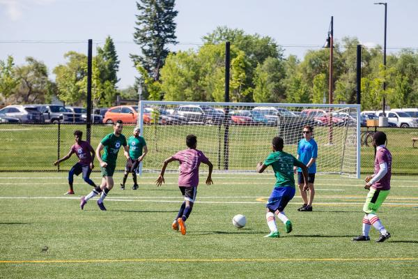 Players race for the soccer ball on a beautiful day in Missoula