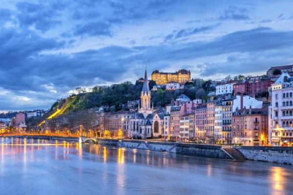 Warm lights glow through the blue hour in Lyon