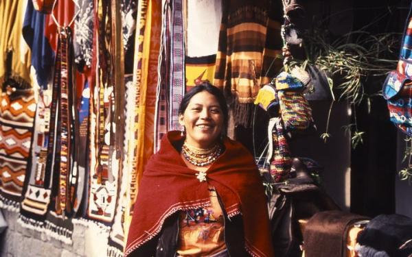 An Indigenous woman shows off her weavings