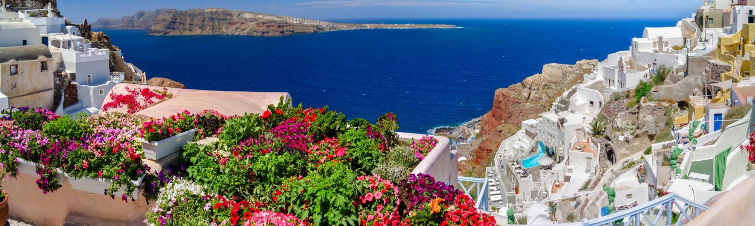 Colorful flowers and brilliant blue skies complement beautiful Greek islands