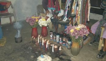 Maximon has candles, flowers, food, and incense