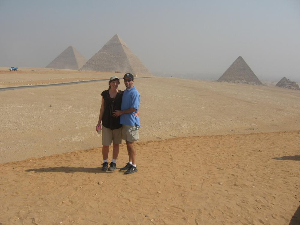 A couple poses in front of the pyramids.