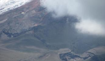 Cotopaxi in the clouds; the glacier used to come all the way down to the Base Camp at the center of the photo