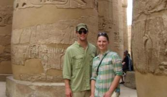 A couple standing amongst egyptian ruins.