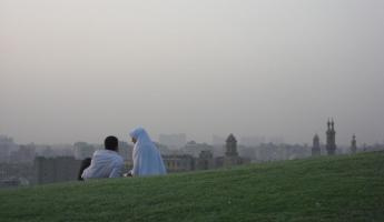 A couple sits on a hill to admire the view.