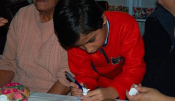 A young boy learning the ancient craft of masapan figurines.