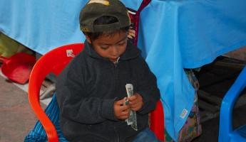 A young entrepreneur counting his money at Otavalo Mkt.