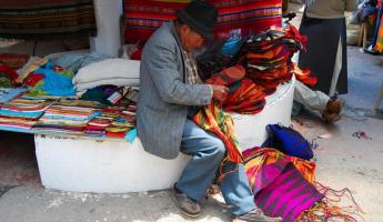 An Ecuadorian man sewing sacks and bags for sale.