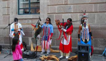 Native Ecuadorians in costumes with instruments