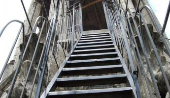 a dizzying climb to the top on metal stairs with gargoyles
