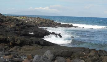 The volcanic rocks rolling in to the surf