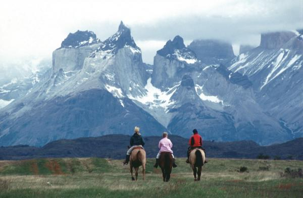 Horseback riding beneath Los Cuernos del Paine