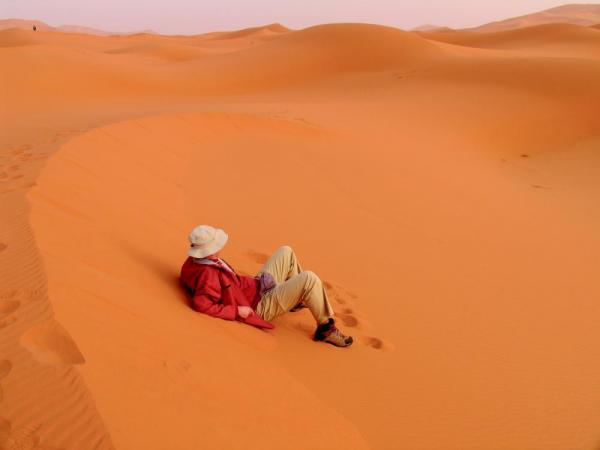 A man rests on the bright red sand of Africa.
