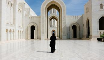 A women in traditional dress walks through the Sultan Qaboos Grand Mosque.