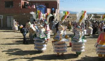 Street party with beautifully costumed dancers on the drive to La Paz
