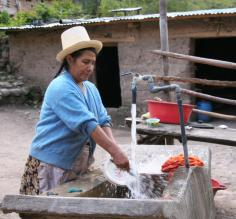 A Quechua woman washes dishes in her courtyard along the Inca Trail