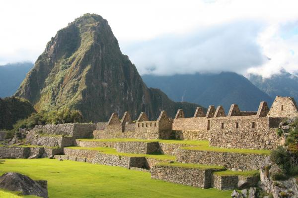 Huayna Picchu rises high behind the Machu Picchu ruins during your Peru tour