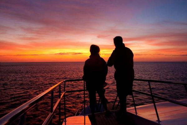 Watch the sun set over the warm Galapagos waters after a day of adventure