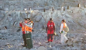 Travelers snapping pictures of the local wildlife on a remote Antarctica tour