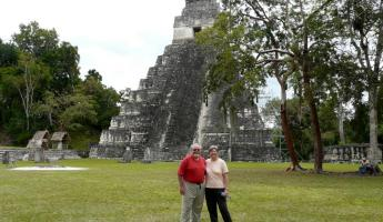 Posing for a picture in front of a temple in Tikal