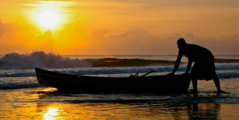 A local fisherman pulls his boat ashore at sunset in Costa Rica