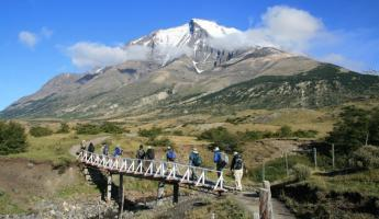 A trekking group crosses a creek in Torres del Paine