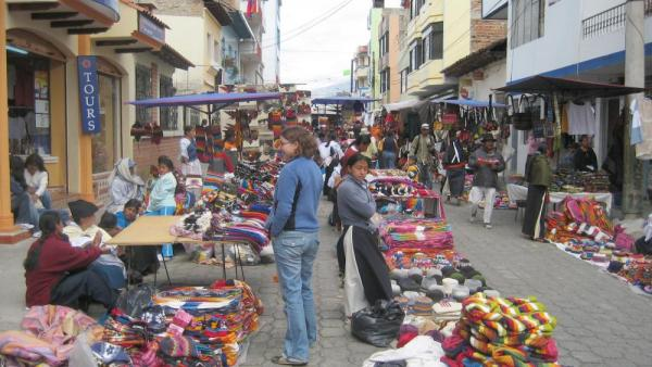 A traveler haggles with an artisan worker at the Otavalo Market