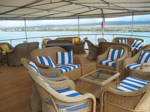 Enjoy the passing scenery from the sun deck on your Galapagos cruise