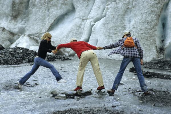 Travelers exploring a glacier on an Alaska tour
