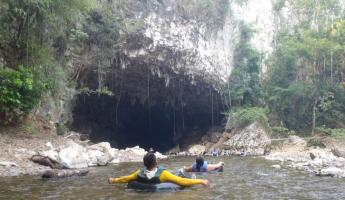 A guided tubing trip enters the mouth of the cave