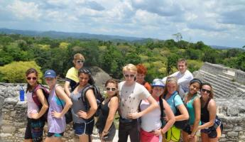 A student group stands atop the temple at Caracol ruins