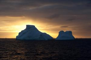 The sun sets over remote icebergs in Antarctica