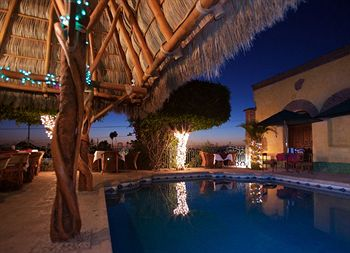 The pool area includes a palapa bar, perfect for enjoying an evening