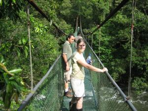 Crossing a suspension bridge while hiking Sarapiqui.