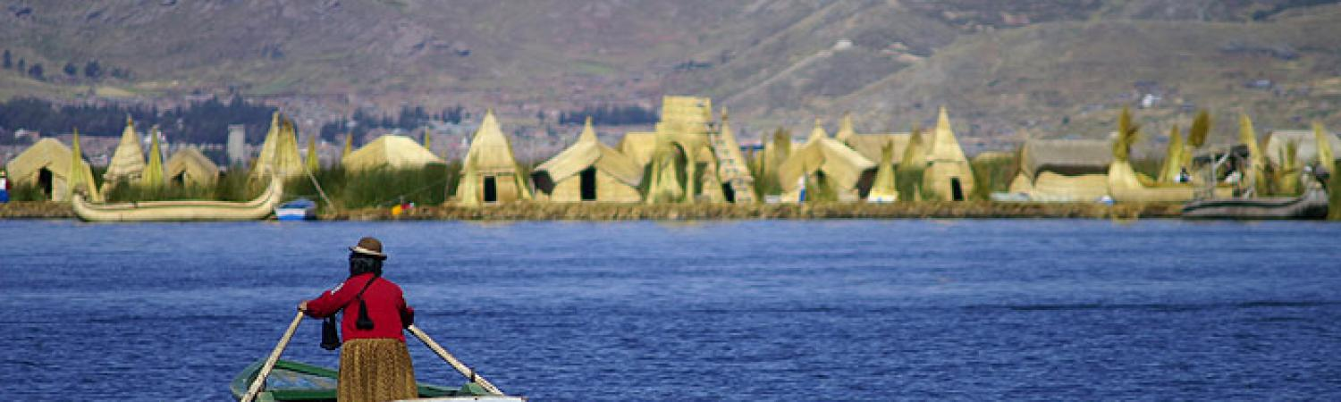 Local Peruvian rows towards shore on Lake Titicaca