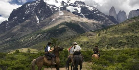 Chilean huasos riding rowards the towers in Torres del Paine