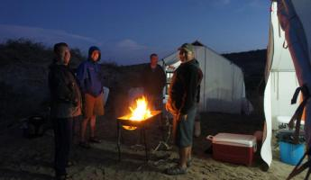 Gathering around the fire while camping in Baja