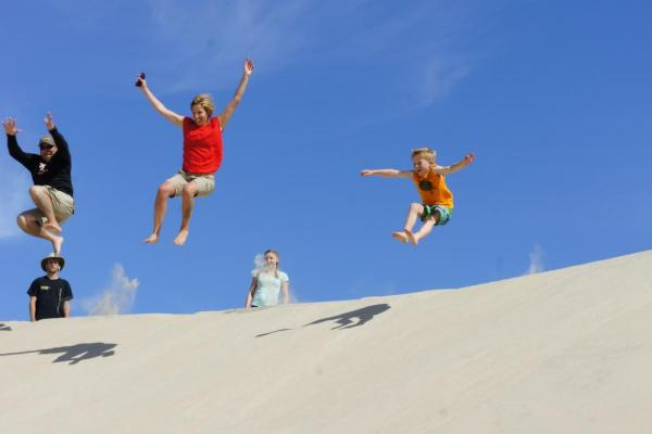 Jumping down a sand dune in Mexico