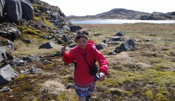 My daughter finds a caribou antler as we hike the terrain