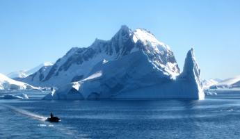 A massive iceberg dwarfs your approach during an Antarctica cruise
