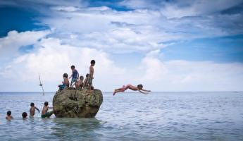 Children dive from the rocks.