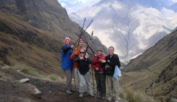 Travelers celebrating on the top of Dead Womans Pass on the Inca Trail
